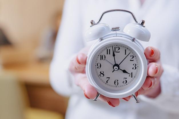 Employé de bureau élégant dans des verres avec un réveil classique dans les mains sur le fond des collègues de travail Photo Premium