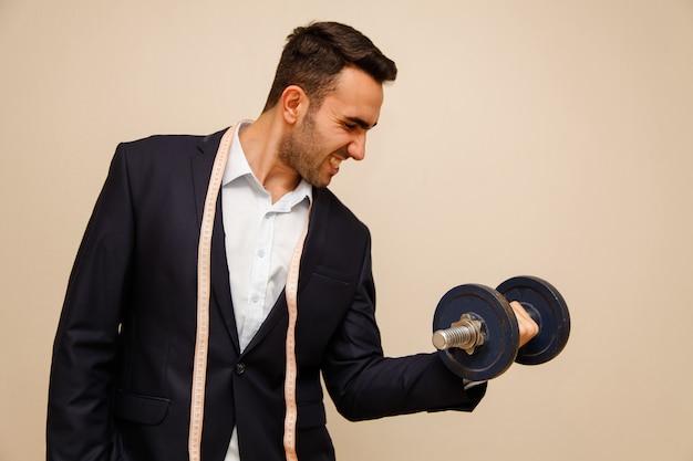 Employé de bureau musculaire mâle tient haltère. travailler dans le concept de bureau. Photo Premium
