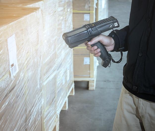 Un employé d'entrepôt tient un lecteur de code à barres avec balayage sur la palette d'expédition Photo Premium