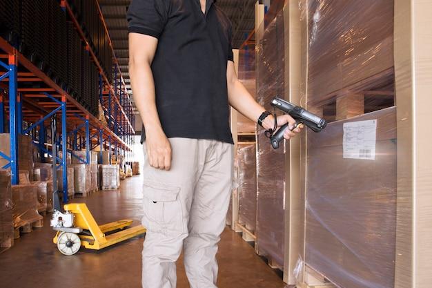 Un employé d'entrepôt tient un lecteur de code à barres avec numérisation des produits. Photo Premium
