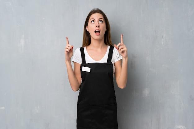 Employé femme surprise et pointant vers le haut Photo Premium