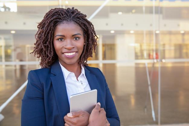 Employé Heureux Avec Tablette Posant Près D'un Immeuble De Bureaux Photo gratuit