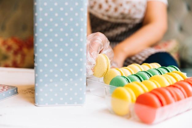 Employé de magasin préparant une boîte à macarons Photo gratuit