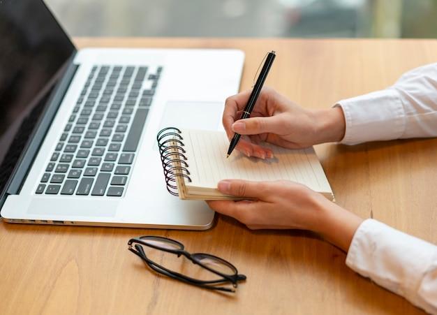 Employé moderne écrit dans le bloc-notes Photo gratuit