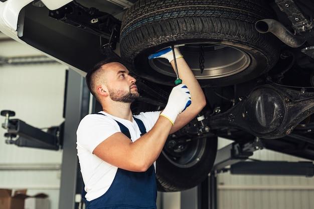 Employé de service automobile vérifiant les roues de la voiture Photo gratuit