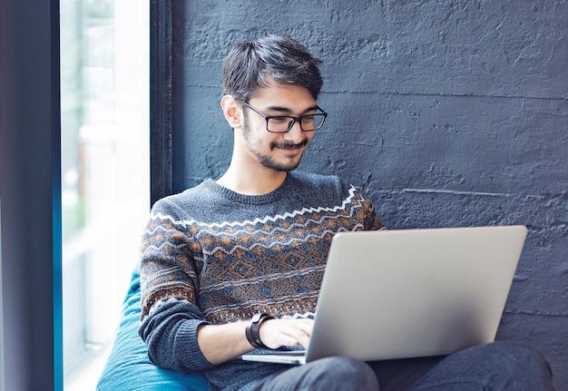 Employé de sexe masculin assis sur un canapé à côté d'une fenêtre avec son ordinateur portable Photo gratuit