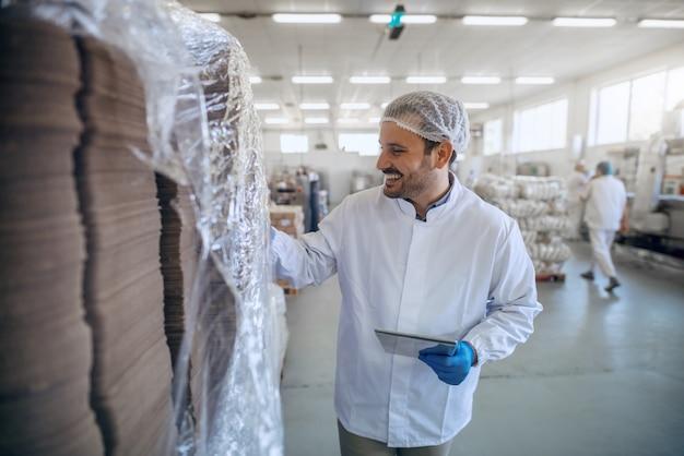 Employé Souriant Caucasien En Uniforme Stérile Blanc à L'aide De Comprimés Dans Une Usine Alimentaire Photo Premium