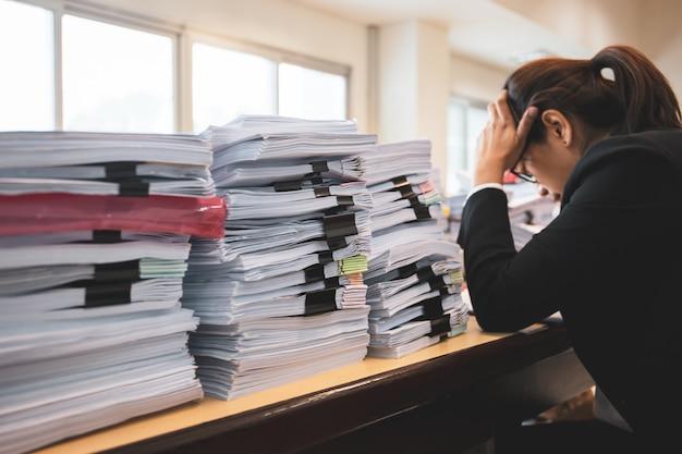 Une employée de bureau est affligée par beaucoup de paperasse sur son bureau. Photo Premium