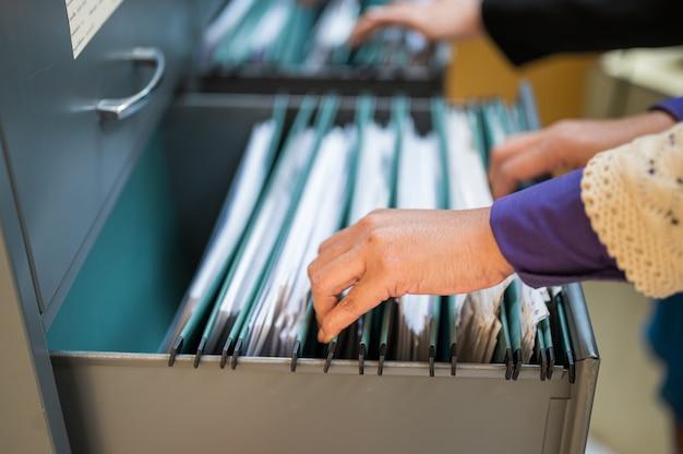 Les employés utilisent leurs mains pour rechercher des documents dans des classeurs Photo Premium