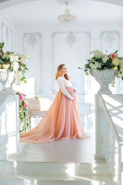 Enceinte dans une robe à la fenêtre, le concept de la maternité Photo Premium
