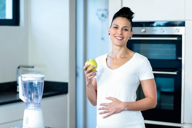 Enceinte Femme Tenant Une Pomme Verte Et Souriant Dans La Cuisine Photo Premium
