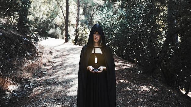 Enchanteresse au cap tenant une bougie dans une forêt ensoleillée Photo gratuit
