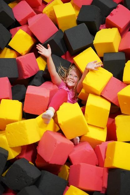 Enfance Heureuse D'un Enfant Moderne Dans La Ville - La Fille Est Allongée Dans De Doux Cubes Dans Un Parc D'attractions Photo Premium