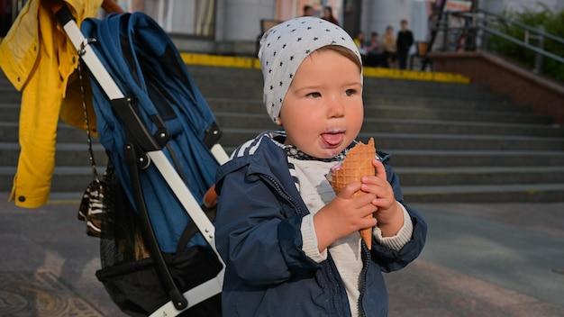 Un Enfant De 1 à 2 Ans Mange Des Glaces Dans La Rue. Fond De Poussette Photo Premium