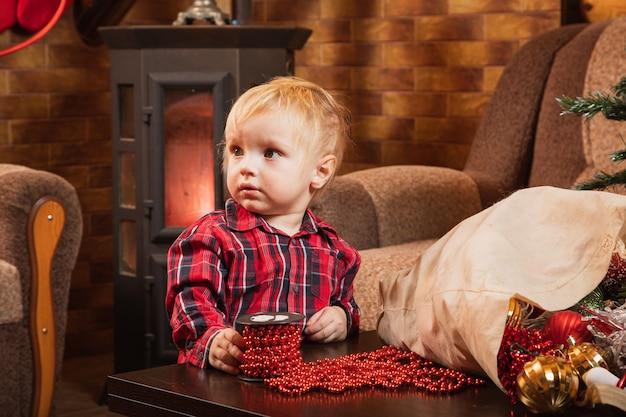 Un Enfant De 1 An Aide à Décorer Un Sapin De Noël Avec Des Perles Rouges. Photo Premium