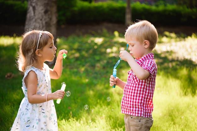 Enfant et amis jouent une bulle dans l'aire de jeu avec coucher de soleil Photo Premium