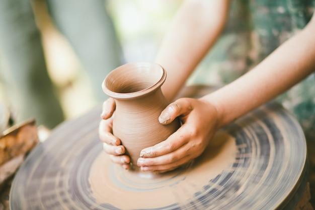 Enfant apprenant à sculpter un pot en argile Photo Premium