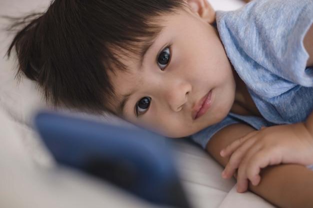Enfant Asiatique, Coucher Lit, Et, Jouer, Sur, Téléphone Portable Photo Premium