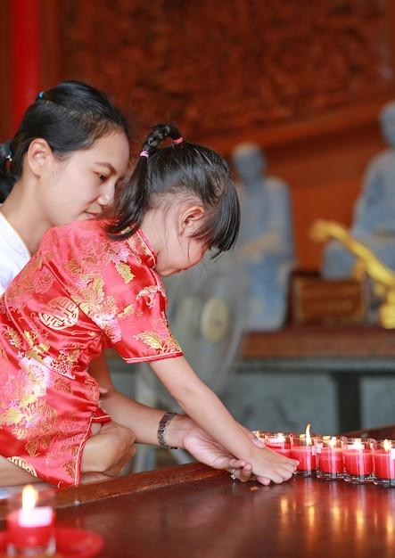 Enfant asiatique fille en costume traditionnel allumer les bougies de culte au temple chinois Photo Premium