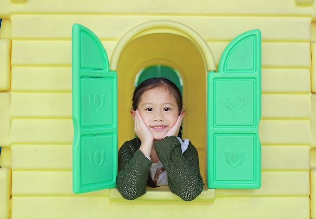 Enfant asiatique fille jouant avec la maison de théâtre jouet fenêtre dans l'aire de jeux. Photo Premium