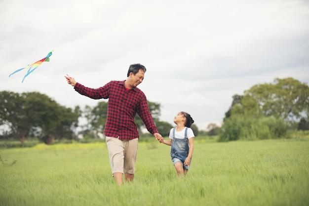 Enfant asiatique fille et père avec un cerf-volant en cours d'exécution et heureux sur prairie en été dans la nature Photo Premium