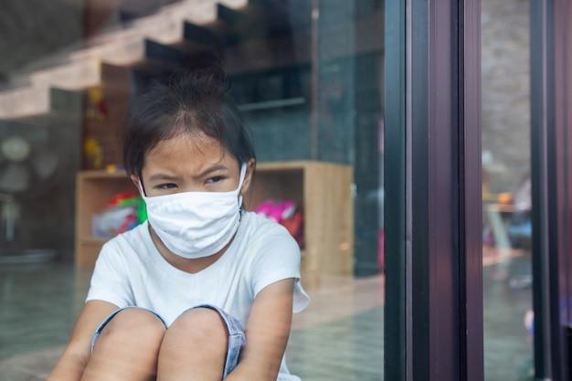 Enfant Asiatique Fille Portant Un Masque De Protection Regardant à L'extérieur Par La Fenêtre Et Rester à La Maison En Quarantaine Contre Le Coronavirus Covid-19 Et La Pollution De L'air Pm2.5. Photo Premium
