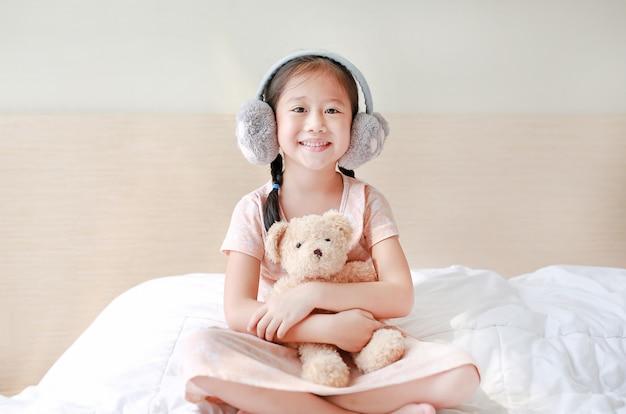 Enfant asiatique, fille, porter, hiver, cache-oreilles et embrassant ours en peluche Photo Premium