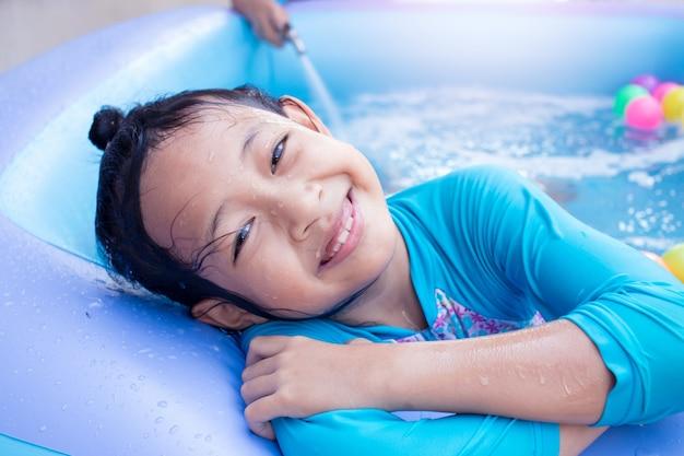 Enfant asiatique fille s'amuser dans la piscine de jardin avec le père remplissent wather en arrière-plan. Photo Premium