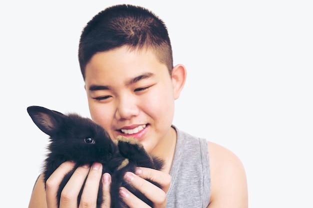 Enfant asiatique jouant avec joli bébé lapin isolé sur blanc Photo gratuit