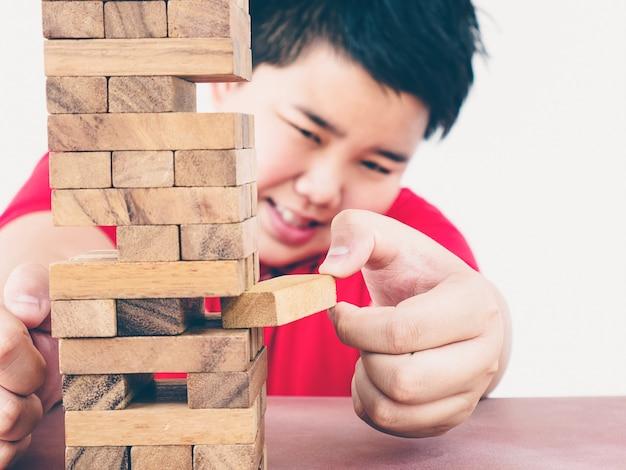 Enfant asiatique joue au jeu de tour de blocs de bois pour la pratique des compétences physiques et mentales Photo gratuit
