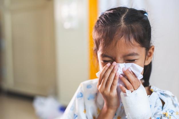 Enfant asiatique malade qui a une solution intraveineuse bandée, essuyant et nettoyant le nez avec un mouchoir sur la main à l'hôpital Photo Premium