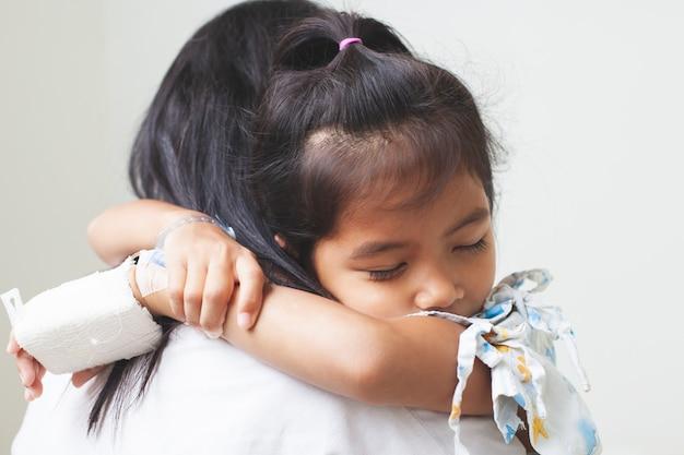 Enfant asiatique malade qui a une solution intraveineuse bandée étreignant sa mère avec amour à l'hôpital Photo Premium