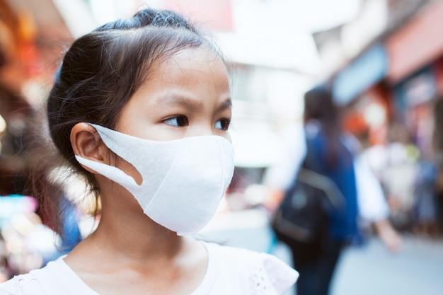 Enfant asiatique mignon portant un masque de protection contre la pollution par le smog atmosphérique Photo Premium