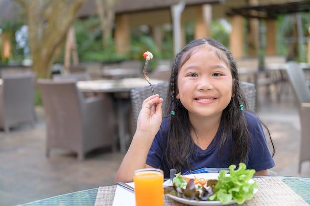 Enfant asiatique profiter de manger une salade de légumes Photo Premium