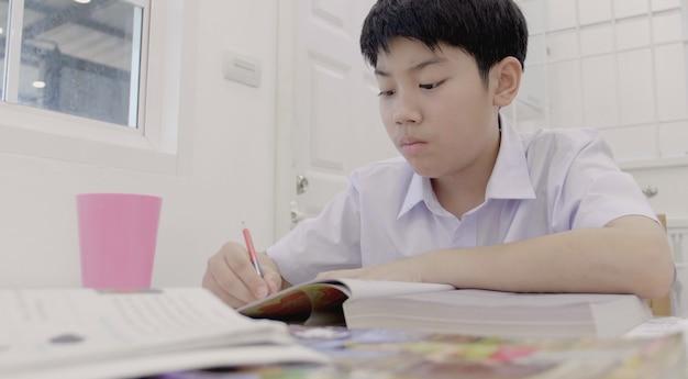Enfant asiatique en uniforme d'étudiant à faire ses devoirs à la maison. Photo Premium