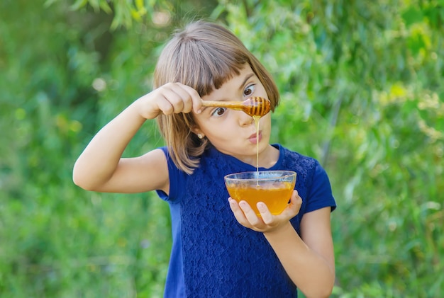 Enfant une assiette de miel dans les mains Photo Premium