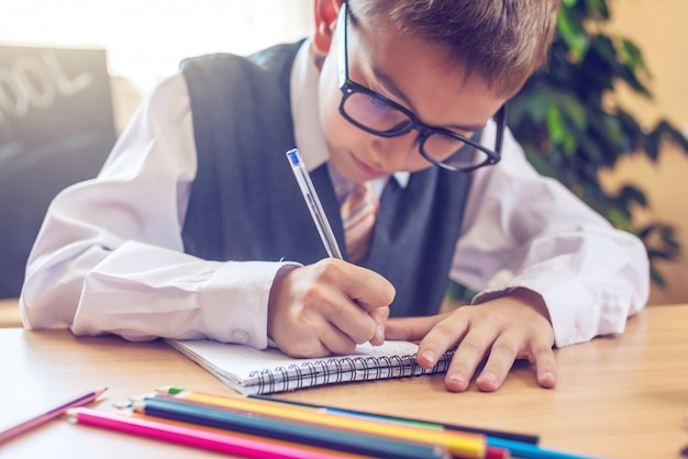 Enfant assis au bureau dans la classe. un garçon apprend des leçons écrit un stylo dans un cahier Photo Premium