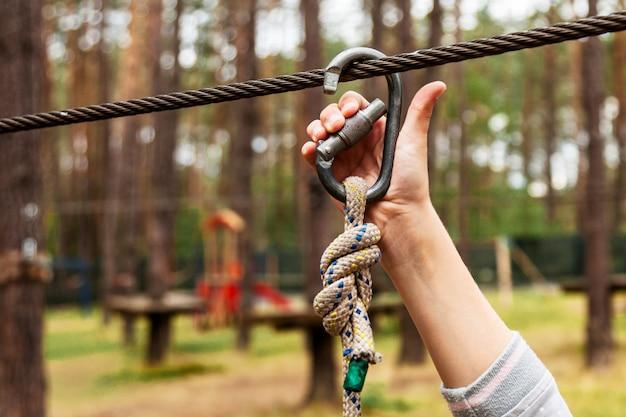 Un enfant attache une carabine sur une corde de sécurité Photo Premium