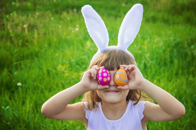 Enfant aux oreilles de lapin. pâques. mise au point sélective. Photo Premium
