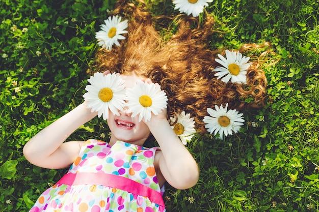 Enfant aux yeux de marguerite couché sur l'herbe verte. Photo Premium