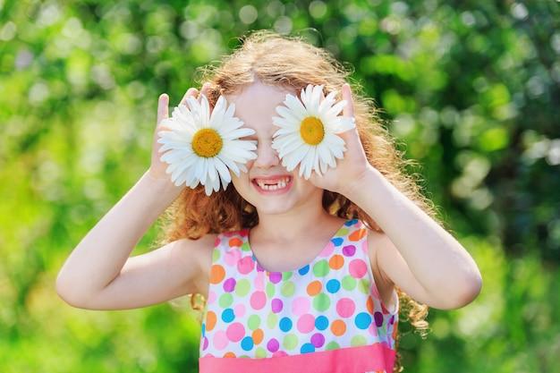 Enfant aux yeux de marguerite, sur fond de bokeh vert Photo Premium