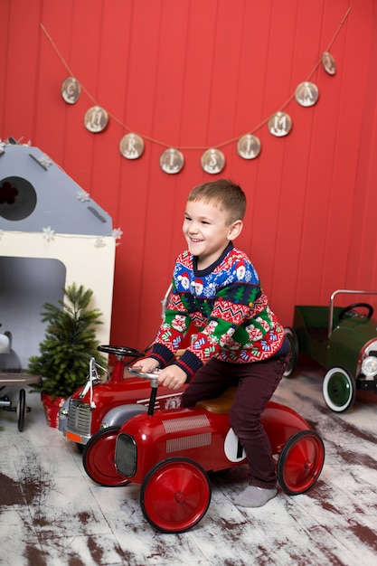 Enfant en bas âge mignon joue avec des voitures rouges de jouet Photo Premium