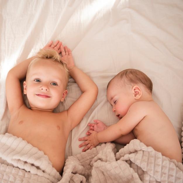 Enfant en bas âge pose à côté de bébé Photo gratuit
