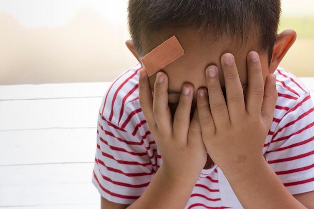 Enfant blessé sur la tête avec un fond blanc en bois Photo Premium