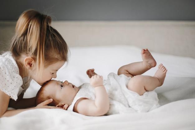 Enfant Blonde Sur La Couverture Blanche Vêtue De Vêtements Blancs Photo gratuit