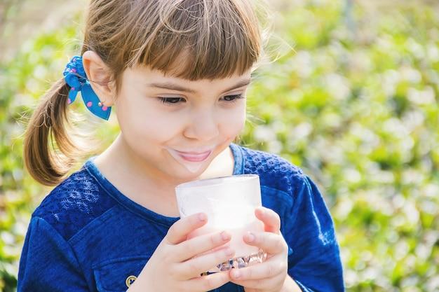 L'enfant boit du lait. mise au point sélective. des gamins. Photo Premium