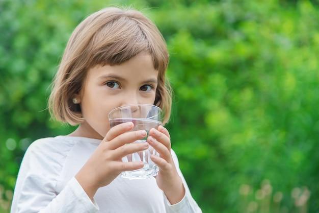 Enfant boit de l'eau dans un verre Photo Premium