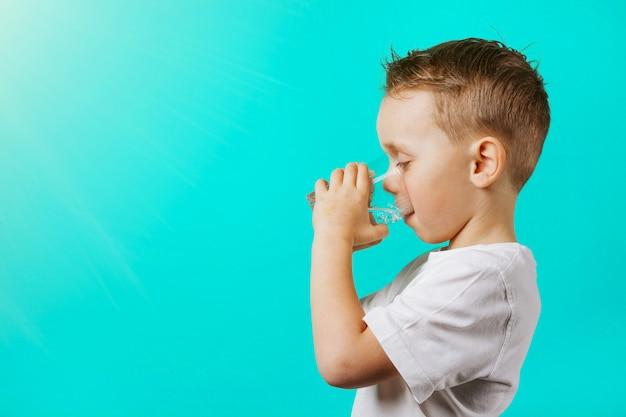 Un Enfant Boit De L'eau Sur Un Fond Turquoise Photo Premium