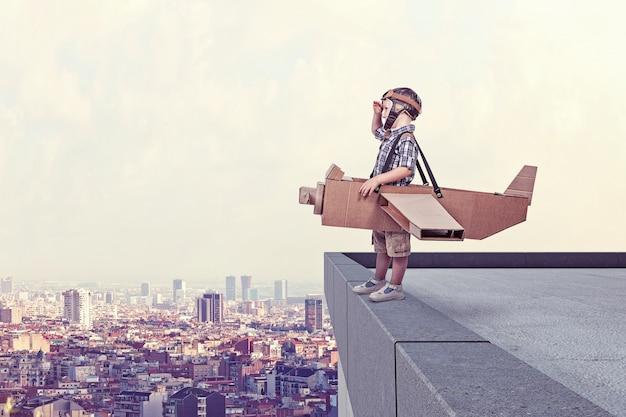 Enfant, carton, avion, sommet, bâtiment, ville, fond Photo Premium