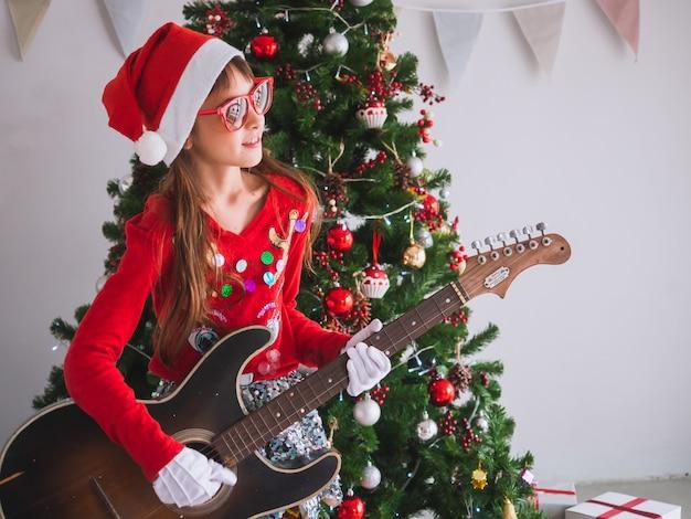 Enfant célébrer noël en gratifiant la guitare dans la maison, une fille joue une chanson avec un sourire le jour de noël Photo Premium